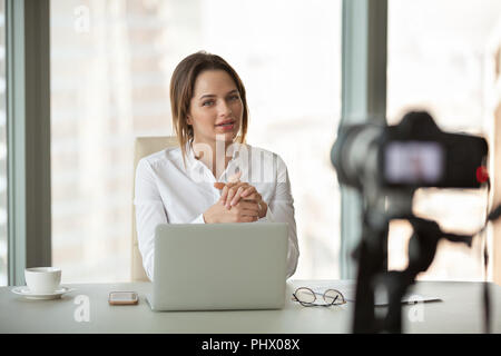 Young businesswoman vlogger recording vlog talking to camera in  - Stock Photo
