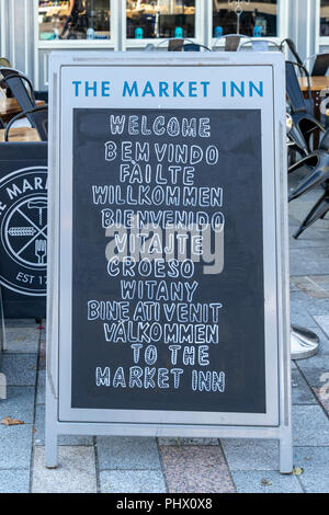 Pub chalk board displaying the word welcome in a number of different languages - Stock Photo
