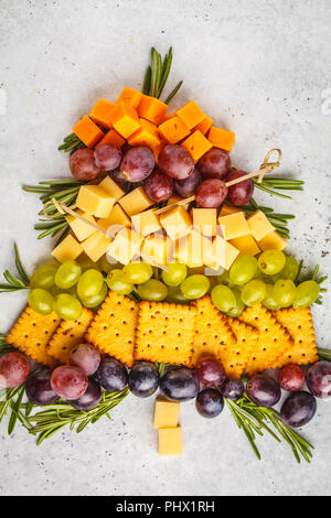 Christmas tree from appetizers: cheese, grapes, crackers. Christmas food concept, white background. - Stock Photo