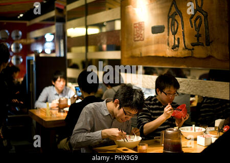 Customers enjoy soup noodles prepared at Hakata Ippudo Ramen's main store in the Daimyo district of Fukuoka City, Fukuoka Prefecture Japan on 08 March - Stock Photo