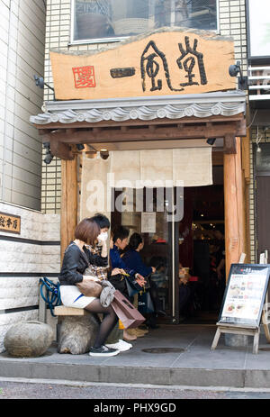 Customers line up to enjoy soup noodles prepared at Hakata Ippudo Ramen's main store in the Daimyo district of Fukuoka City, Fukuoka Prefecture Japan  - Stock Photo
