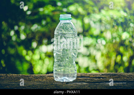 crushing used a plastic bottle on old wood table - Stock Photo