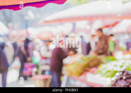 Blurred background of people shopping at fresh market fair in sunny day.blur background with bokeh