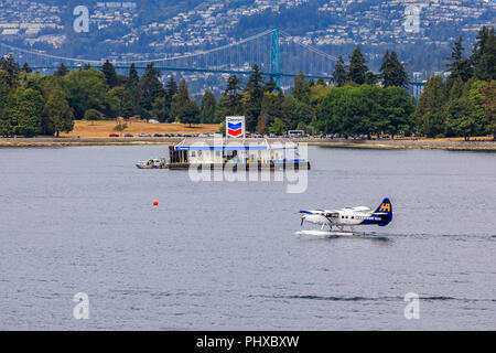 Vancouver, Canada - August 04, 2018:  De Havilland Beaver sea plane passing the fueling station in Vancouver Harbour - Stock Photo