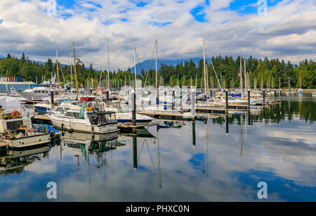 Vancouver, Canada - August 04, 2018 - Luxury boats docked at Coal Harbor on a cloudy day with Stanley Park and Grouse Mountain  in the background - Stock Photo
