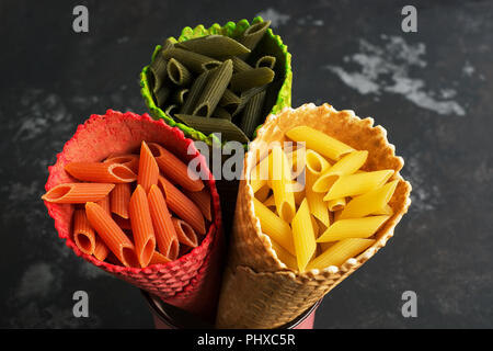 Colored macaroni close-up in waffle colored horns. The concept of color and food. View from above, flat lay - Stock Photo