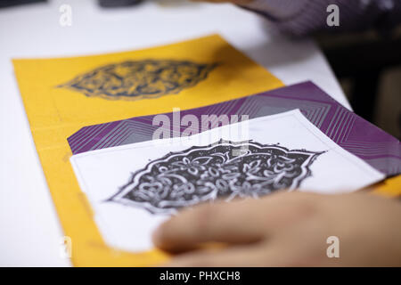 Book binder hand illustrating book covers in his workshop calligraphic patterns at his work table in a close up view - Stock Photo
