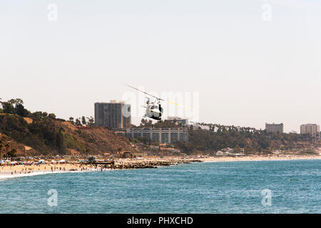 A view of a flying fire helicopter over the Malibu beach in summer time in California - Stock Photo