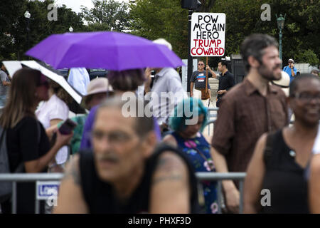 August 31, 2018 - Washington, District of Columbia, U.S. - A demonstrators holds a protest sign as mourners line up outside the United States Capitol to pay their respects to former Senator John McCain, Republican of Arizona, as he lays in state in the Rotunda of the Capitol in Washington, DC on August 31, 2018 in Washington, DC. McCain, a United States Military veteran and longtime Senator, will lay in state inside the Capitol Rotunda for one day prior to being laid to rest on September 1, 2018 at the United States Naval Academy in Annapolis, Maryland. Credit: Alex Edelman/CNP (Credit Image - Stock Photo