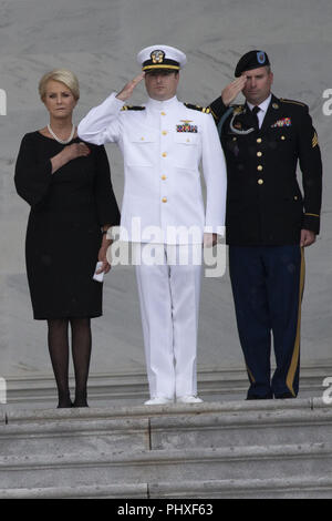 August 31, 2018 - Washington, District of Columbia, U.S. - Cindy McCain and her sons Jack, center, and jimmy, right, stand at attention as a United States Military Honor Guard carries the casket of former Senator John McCain, Republican of Arizona, up the stairs of the Capitol in Washington, DC on August 31, 2018 in Washington, DC. McCain, a United States Military veteran and longtime Senator, will lay in state inside the Capitol Rotunda for one day prior to being laid to rest on September 1, 2018 at the United States Naval Academy in Annapolis, Maryland. Credit: Alex Edelman/CNP (Credit Ima - Stock Photo