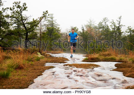 Couple jogging in forest river - Stock Photo