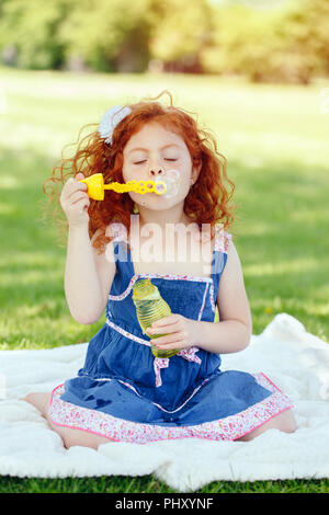 Portrait of cute funny little red-haired Caucasian girl toddler in blue dress in park outside, child blowing soap bubbles, bright summer day, lifestyl - Stock Photo