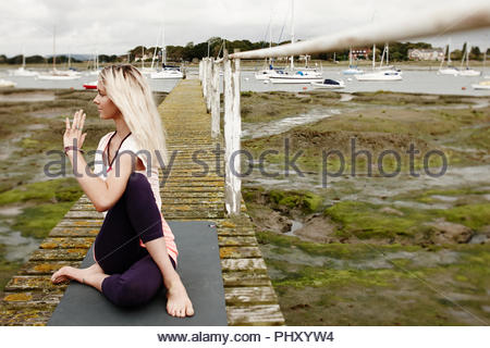 Young woman doing yoga on wooden pier by marina - Stock Photo