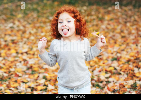 Portrait of cute adorable little red-haired Caucasian girl child making funny silly faces, showing tongue, in autumn fall park outside, playing having - Stock Photo