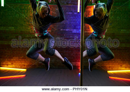 Young woman jumping by a mirror - Stock Photo