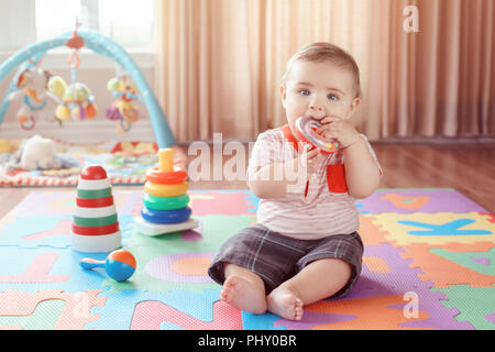 Portrait of cute adorable blond Caucasian smiling child boy with blue eyes sitting on floor in kids children room chewing ring. Little baby playing wi - Stock Photo