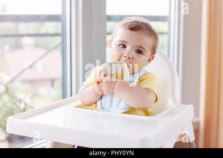Portrait of cute adorable Caucasian child boy with dirty messy face sitting in high chair eating apple puree with fingers. Everyday home childhood lif - Stock Photo