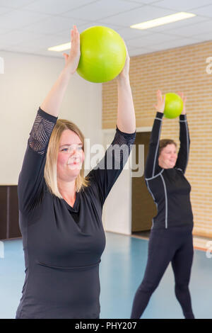 Two dutch caucasian women exercising with balls in gym class - Stock Photo