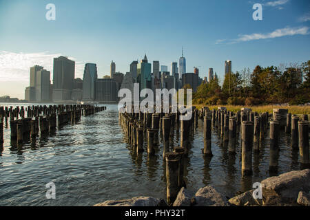 A view of the financial district in Manhattan from the Brooklyn bridge park at sunset. The pilings of an old dock reflect the light of the setting sun - Stock Photo