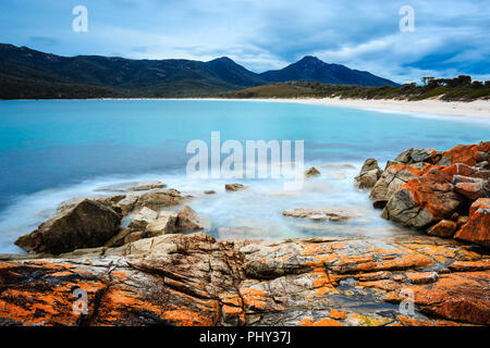 Daytime long exposure capture of Wineglass Bay in Freycinet National Park, Tasmania, Australia, with orange lichen on granite rocks in the foreground. - Stock Photo