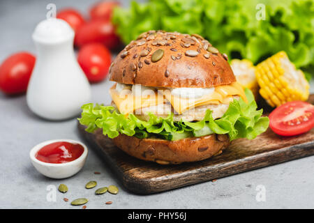 Chicken cheeseburger on wooden serving board on concrete background. Closeup view - Stock Photo