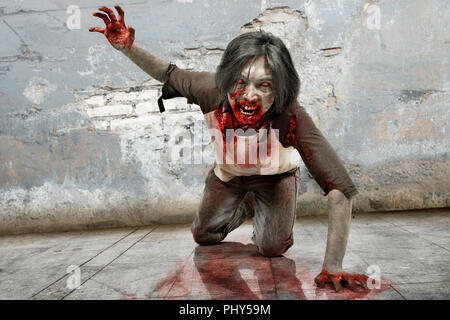 Angry zombie man with bloody mouth crawling over grunge wall background - Stock Photo