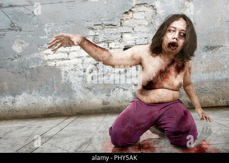 Spooky zombie man with wound on his body posing against grunge wall background - Stock Photo