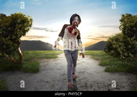 Angry zombie man with bloody mouth walk around at outdoor. Halloween concept - Stock Photo