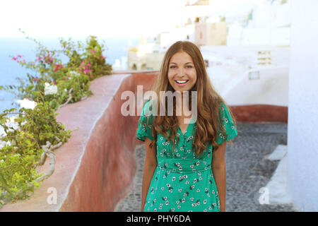 Santorini travel tourist woman visiting famous white village of Oia. Smiling tanned girl in green dress climbs the stairs in Santorini, Cyclades, Gree - Stock Photo