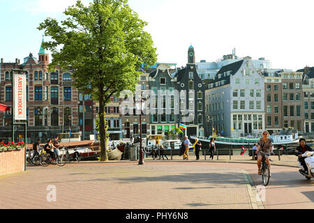 AMSTERDAM, NETHERLANDS - JUNE 6, 2018: beautiful view of Amsterdam street with people on bikes and typical dutch houses - Stock Photo