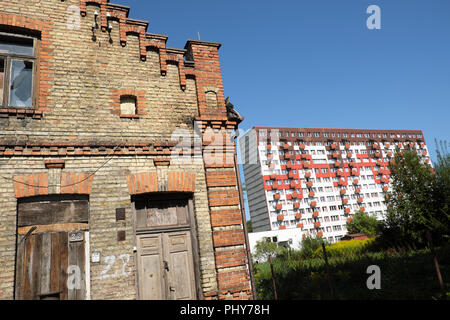 Bialystok Poland contrast between old derelict brick built property and modern high rise block of flats - Stock Photo