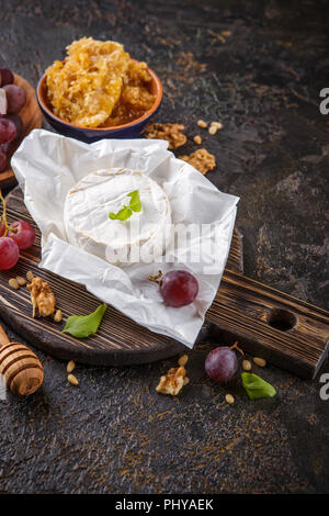 Cheese with honey, nuts and grapes - Stock Photo