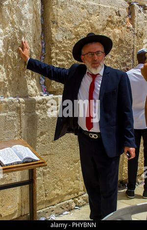 10 May 2018 An Orthodox Jewish male in a traditional dark suit and hat  touching the Western Wall in jerusalem Israel - Stock Photo