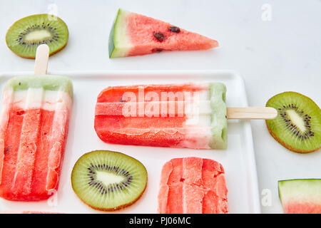 Watermelon ice cream on a stick presented with pieces of kiwi and juicy pieces of watermelon in a plate on a gray marble background. Summer dessert - Stock Photo
