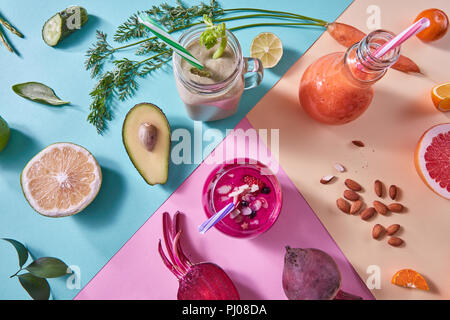 Orange, green and red smoothies from colorful natural vegetables and fruits in a glass bottles with plastic straws on a tricolor background. Top view. - Stock Photo