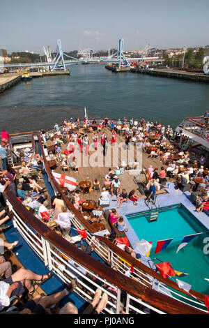 Portugal, Porto, Matosinhos, Leixoes, passengers being entertained on rear deck of MV Marco Polo in sunshine - Stock Photo