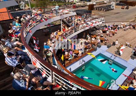 Portugal, Porto, Matosinhos, Leixoes Harbour, MV Marco Polo, passengers on deck around swimmong pool in sunshine - Stock Photo
