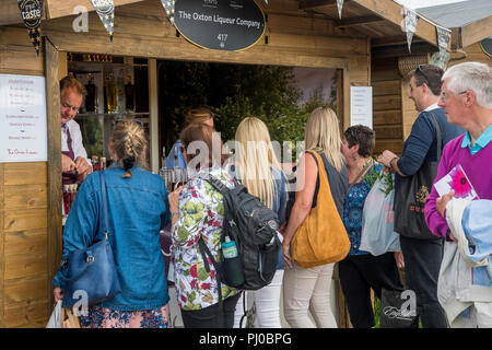 People being served, buying & queuing for handmade liqueurs in glass bottles at trade stand hut - RHS Chatsworth Flower Show, Derbyshire, England, UK. - Stock Photo