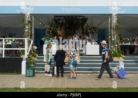 People at showground, walking past, standing by or sitting in Wedgewood refreshment marquee - RHS Chatsworth Flower Show, Derbyshire, England, UK. - Stock Photo