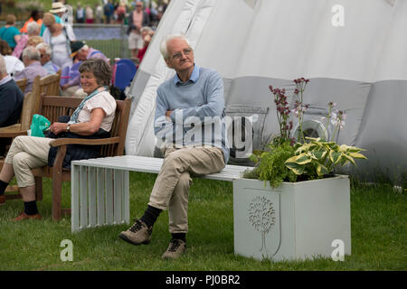 Senior man sitting alone on white bench seat, arms folded & legs crossed, crowd of people beyond - RHS Chatsworth Flower Show, Derbyshire, England, UK - Stock Photo