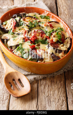 Summer recipe for eggplant casserole with tomatoes, herbs and cheese close-up in a baking dish on a table. vertical - Stock Photo