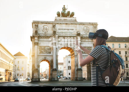 Girl tourist in glasses virtual reality. Virtual trip to Germany. The concept of virtual tourism. Sightseeing Triumphal arch in Munich in the background. - Stock Photo