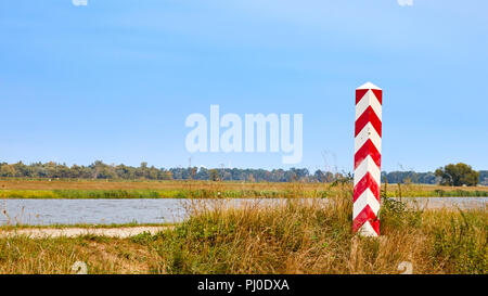 Border pole by the Odra River, which is a natural borders between Poland and Germany. - Stock Photo