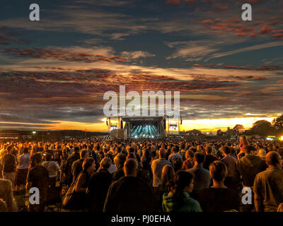 Large crowd watching music on a stage at sunset at a festival in Bristol ( The Downs ) summer vibes. - Stock Photo
