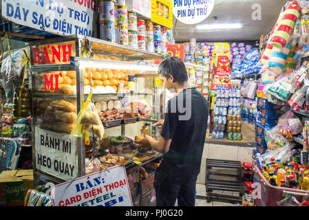 Ho Chi Minh City, Vietnam - May 1, 2018: Young man cooks banh mi using ingredients (bread & sorts of meat) from a street food cart in street at night. - Stock Photo