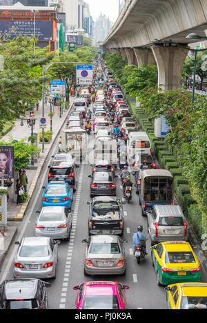 Traffic jam on Sukhumvit Road, near BTS station Phrom Phong, Bangkok, Thailand. BTS and its concrete pillars on right. Vertical. - Stock Photo