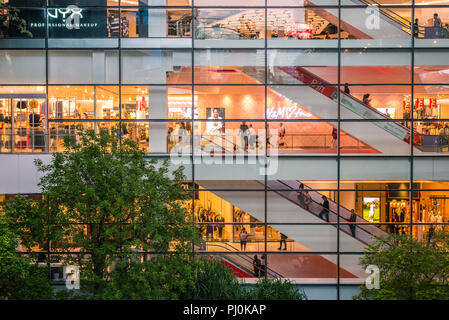 Life of EmQuartier Shopping Mall (Bangkok, Thailand) through the glass at night, and trees of the courtyard garden in the dusk. - Stock Photo