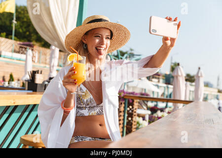 Photo of cheerful young woman 20s in straw hat smiling and taking selfie on mobile phone with orange juice in hands sitting in beach bar during summer - Stock Photo