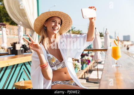 Photo of beautiful young woman 20s in straw hat and swimwear taking selfie on smartphone while drinking orange juice in beach bar during vacation - Stock Photo