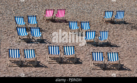 Deckchairs lined up on a pebble beach at the seaside. There are no people in the photograph. Two of the striped chairs are a different colour - Stock Photo
